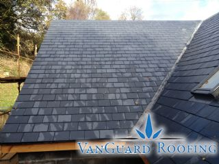 A partial view of a recently completed roof  This photo shows a natural slate covering with a lead valley and roof windows as examples of roof detail